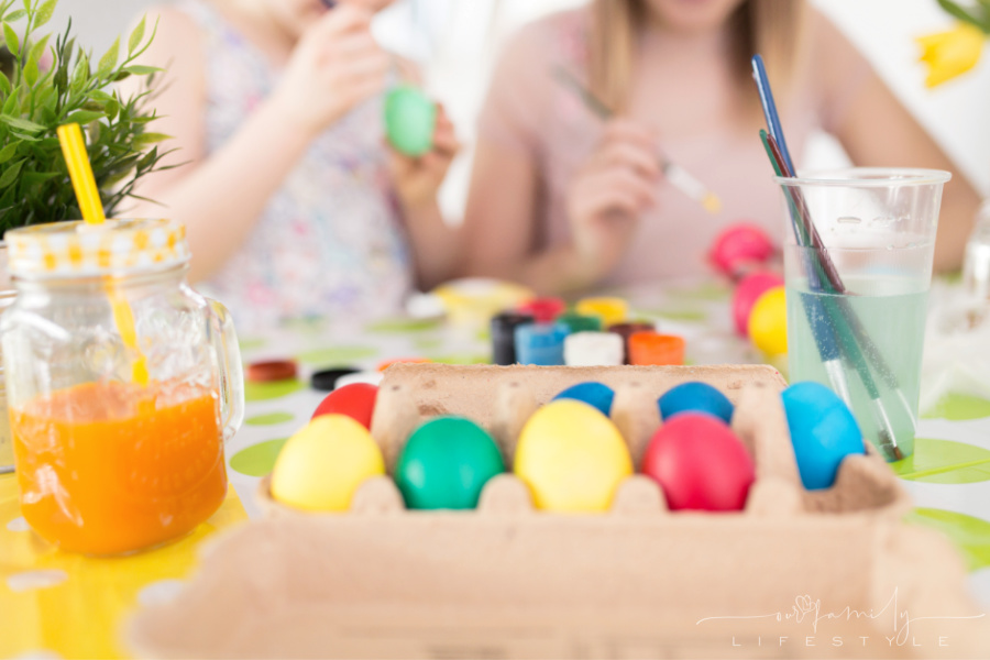 happy sisters painting colorful Easter eggs