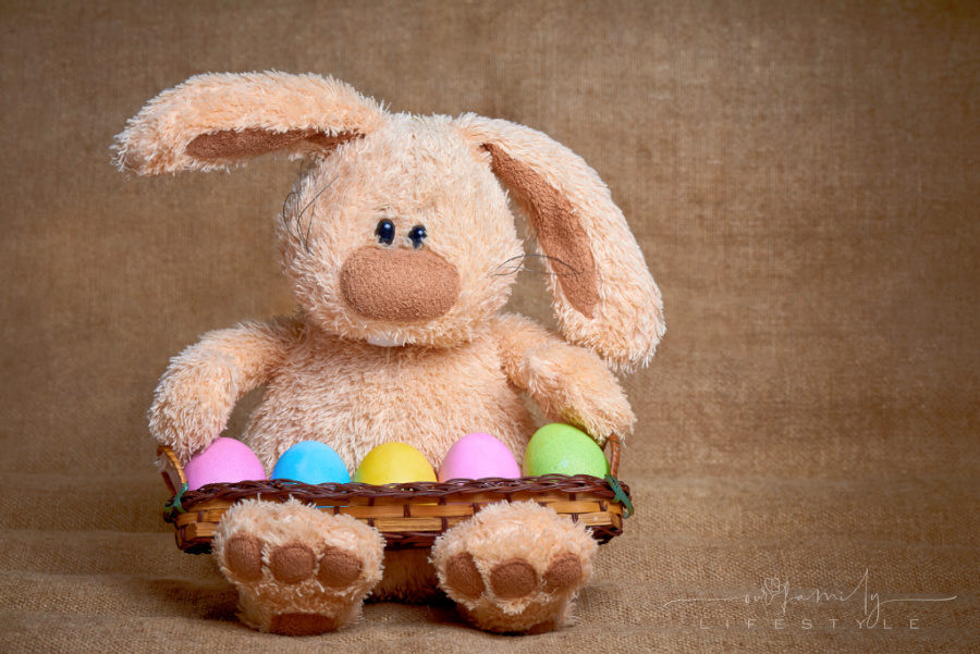 Stuffed soft rabbit with colorful bright painted eggs.