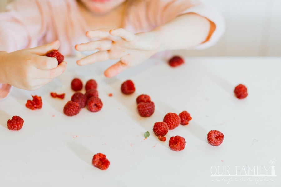 child eating fresh raspberries
