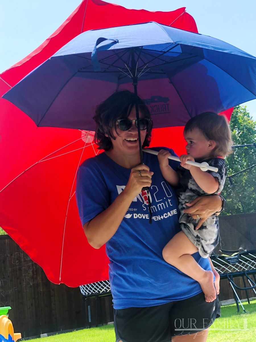 grandma holding two umbrellas with toddler