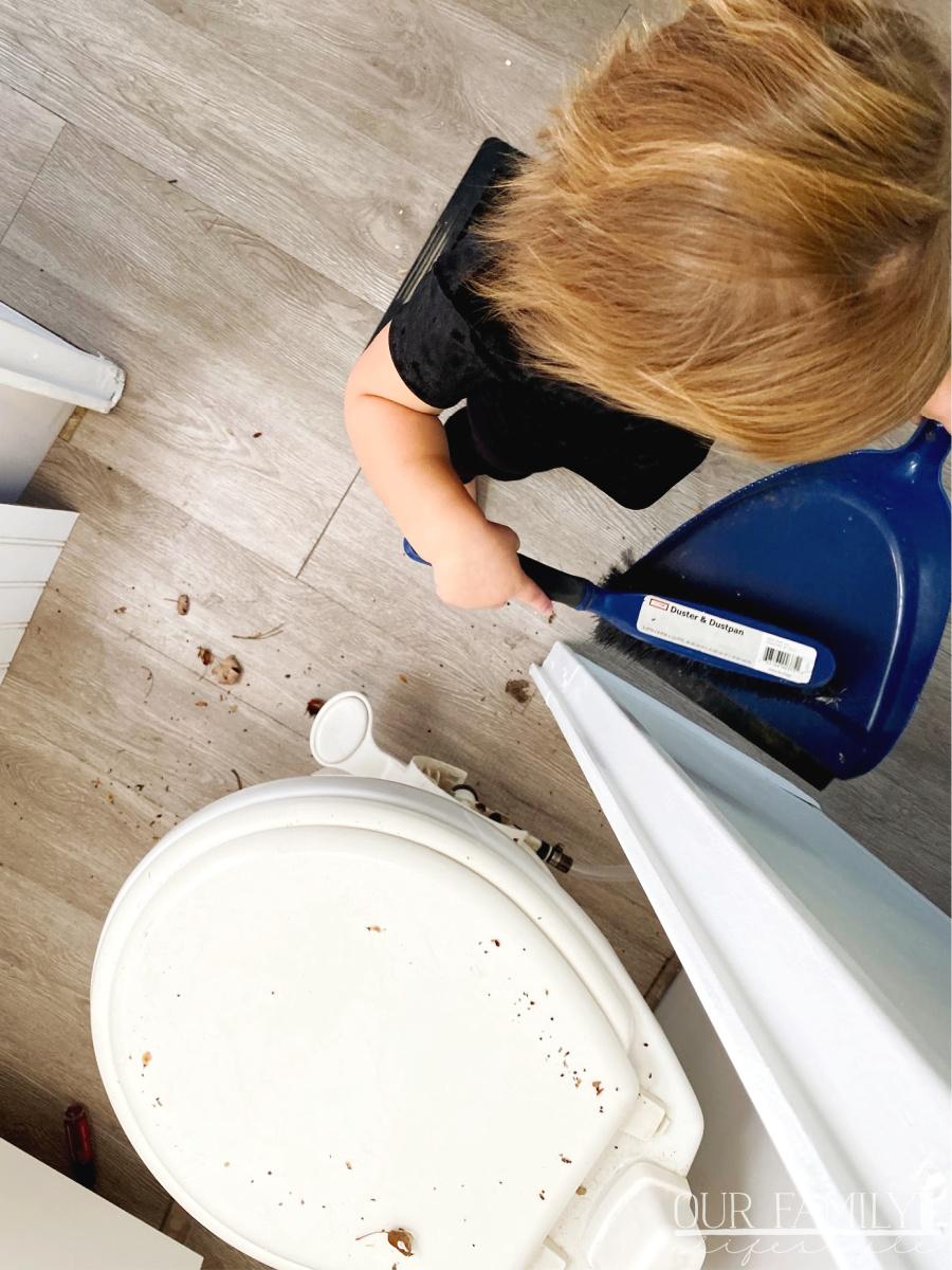 toddler helping sweep floors