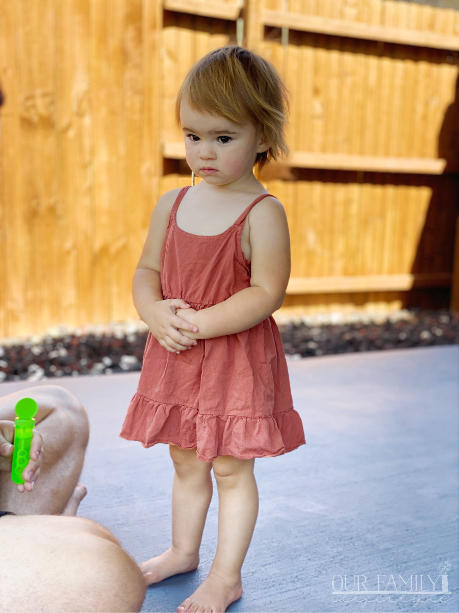 toddler holding her hands on belly