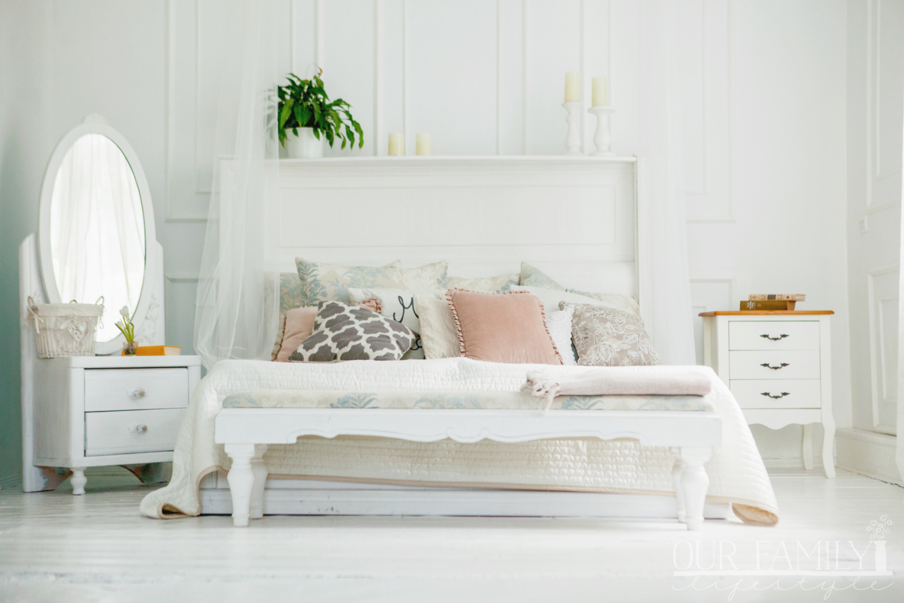 Scandinavian style white bedroom. Four pillows are on the bed. Modern interior.