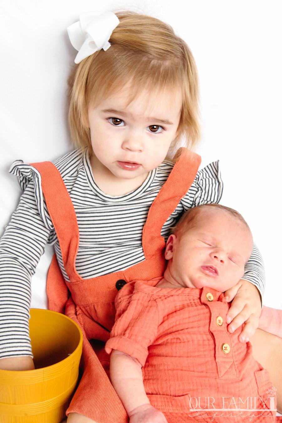 toddler and newborn baby in orange
