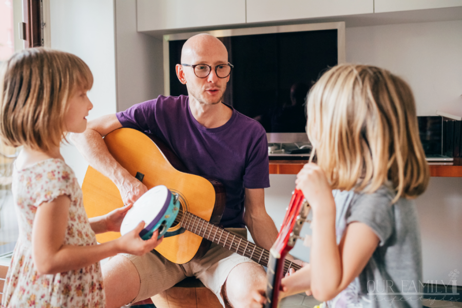 father teaching daughters how to play guitar