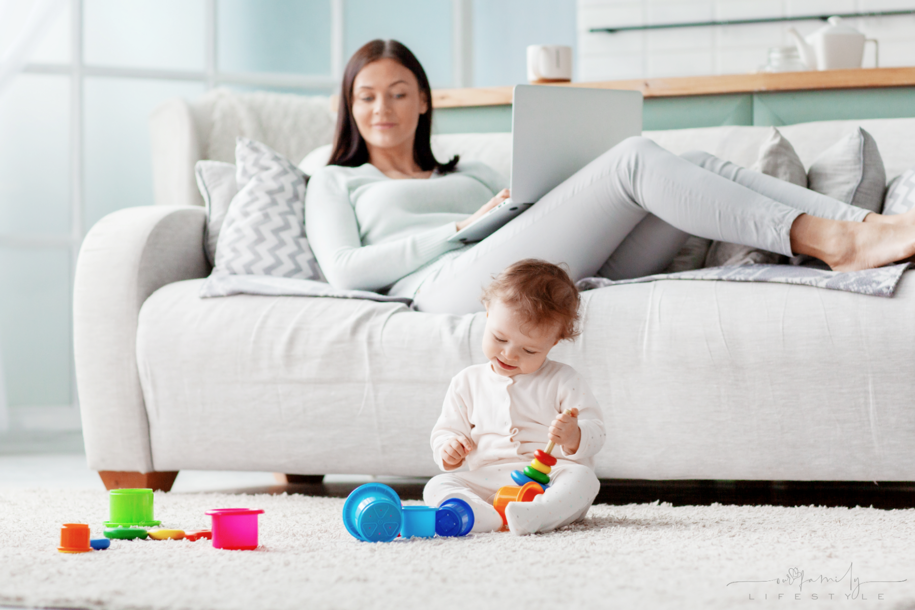 mom-works-laptop-home-while-her-child-plays-with-toys-floor