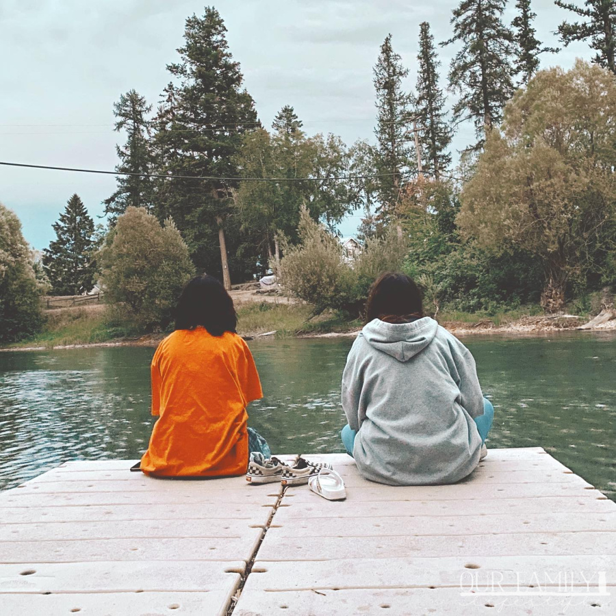 teens sitting on a river dock