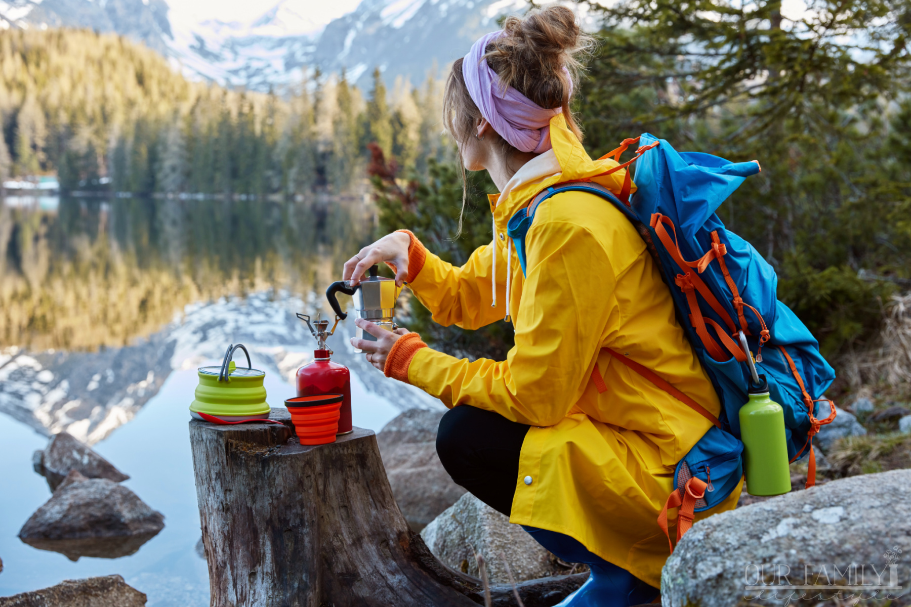 woman overlooking mountain lake with camping gear in hand