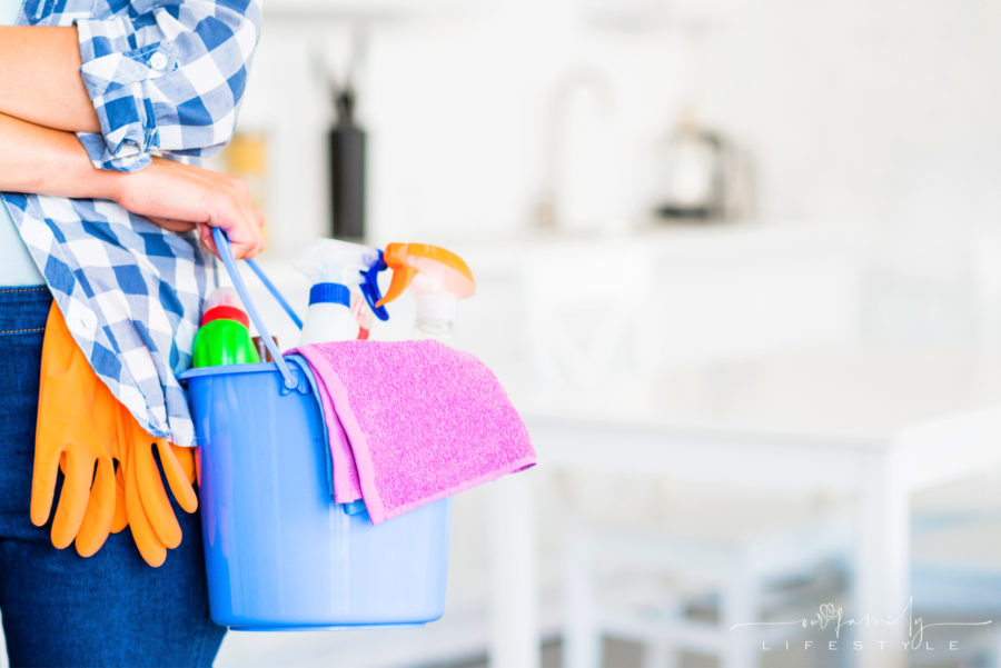 close-up-woman-holding-bucket-with-cleaning-supplies