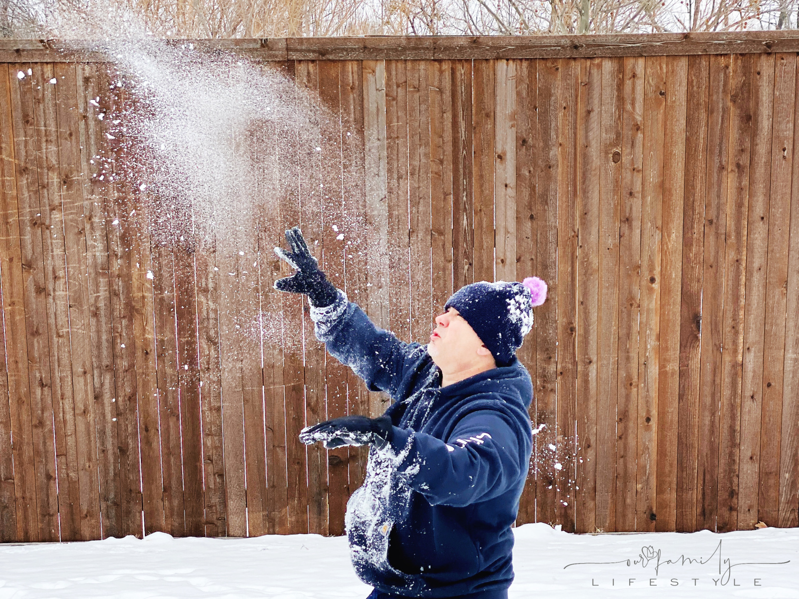 dad throwing powdery snowball at kids