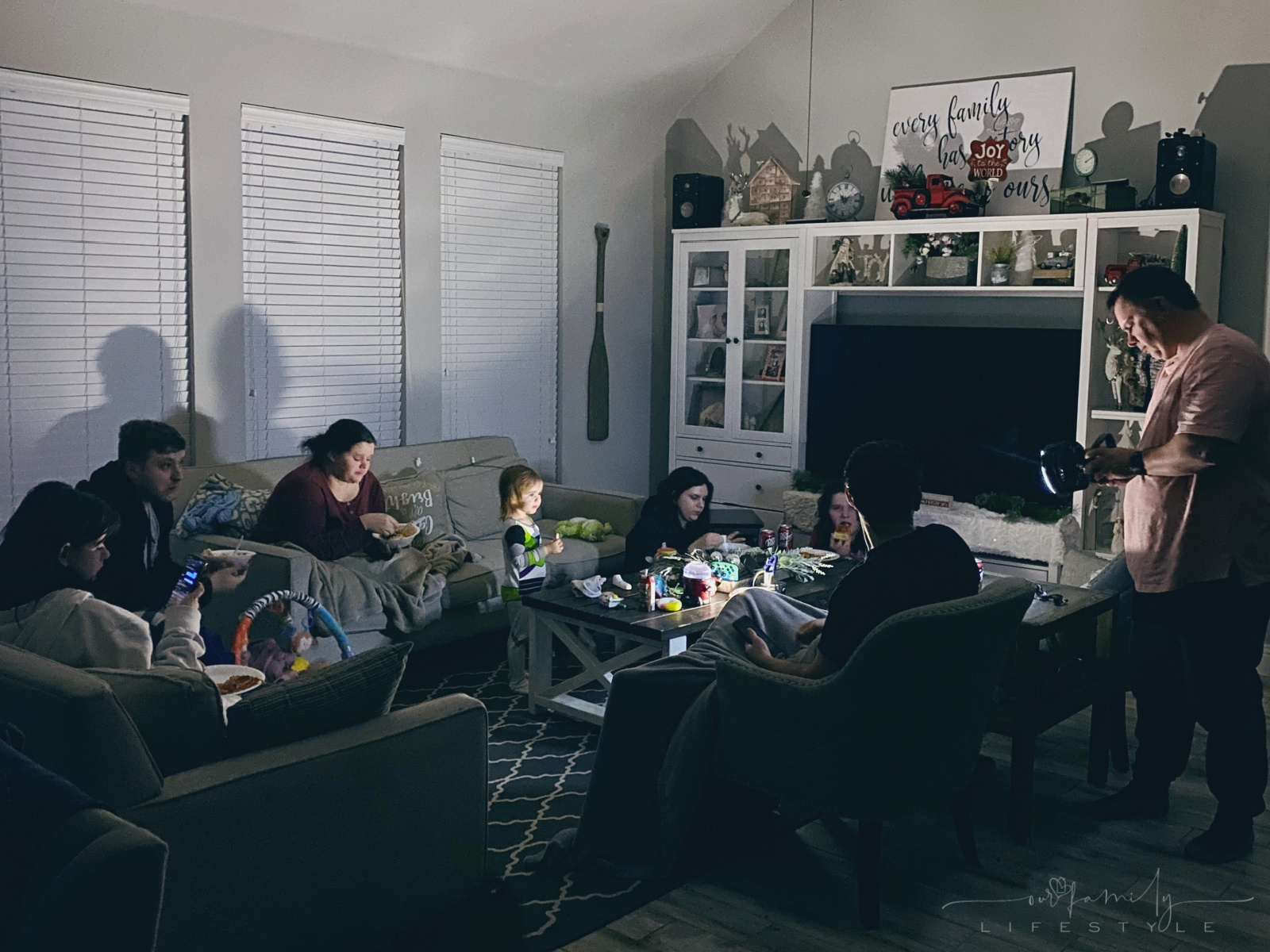 family sitting in dark during Texas power outage