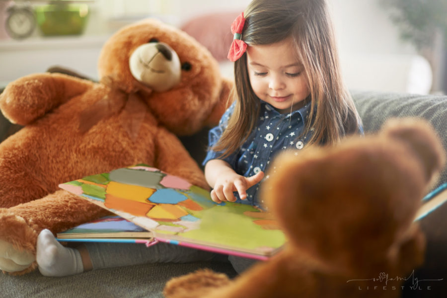 little-girl-reading-book-with-her-teddy-bears