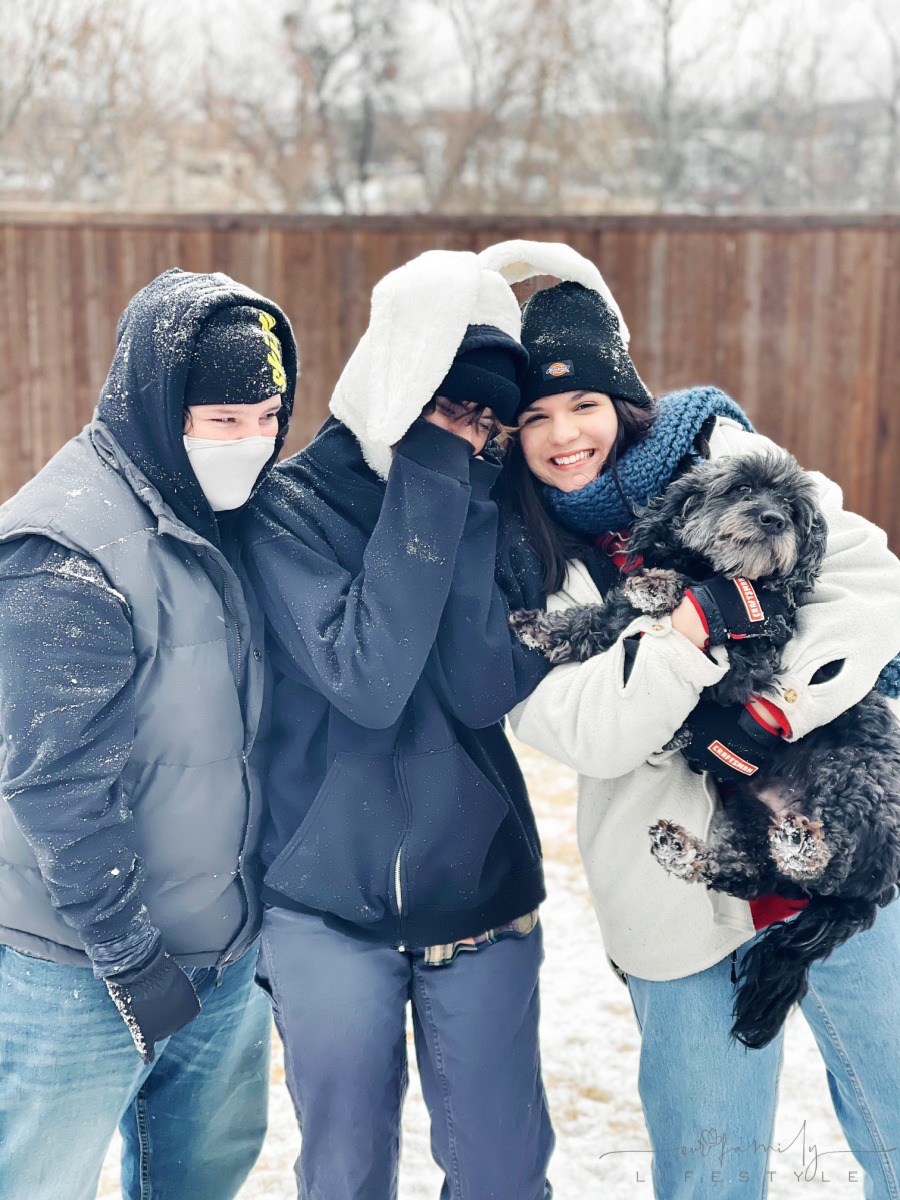 three teens and a goldendoodle standing in the snow