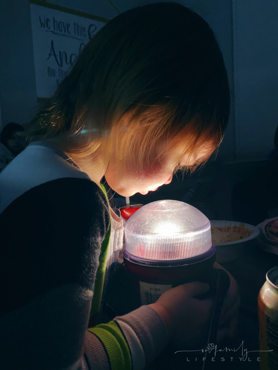 toddler looking into camping lantern during power outage
