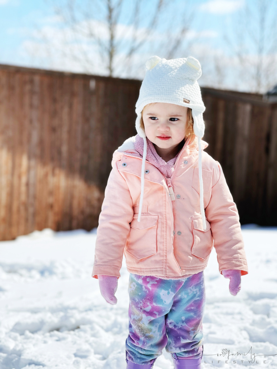 toddler standing in snow with socks on hands