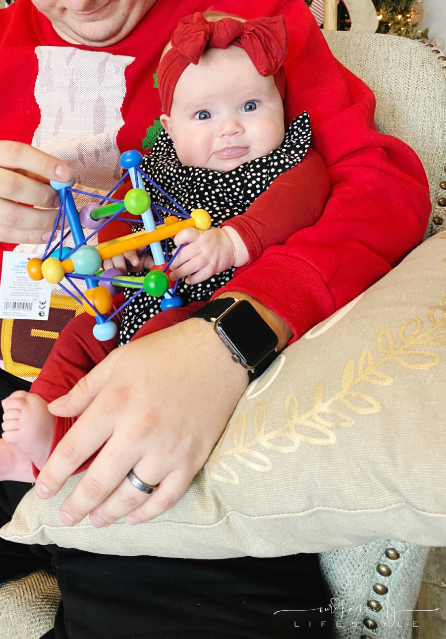 baby holding infant development toy