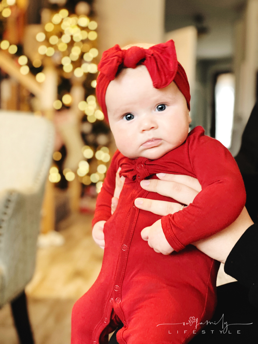 baby in red sleeper and bow looking at camera with bokeh holiday lights in background