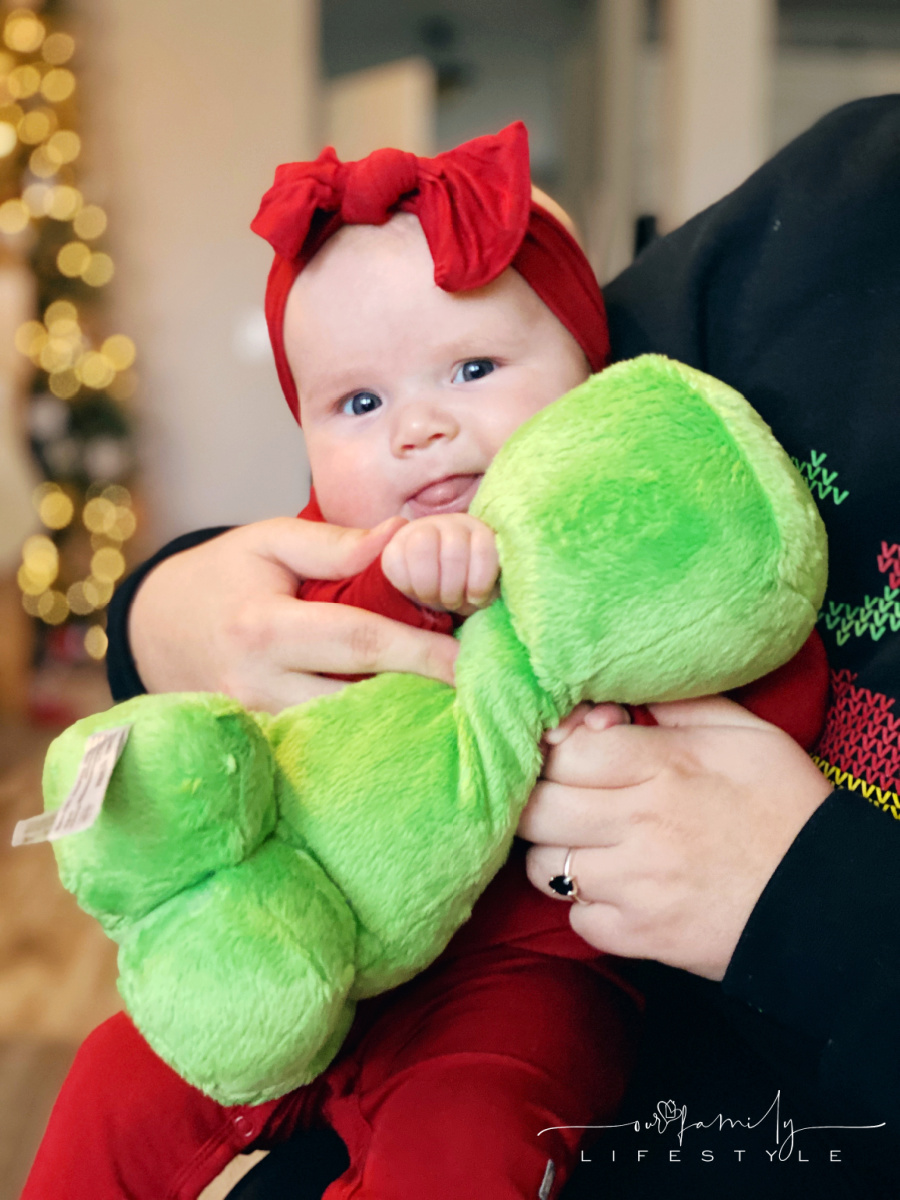 baby with red bow holding a plush minecraft creeper