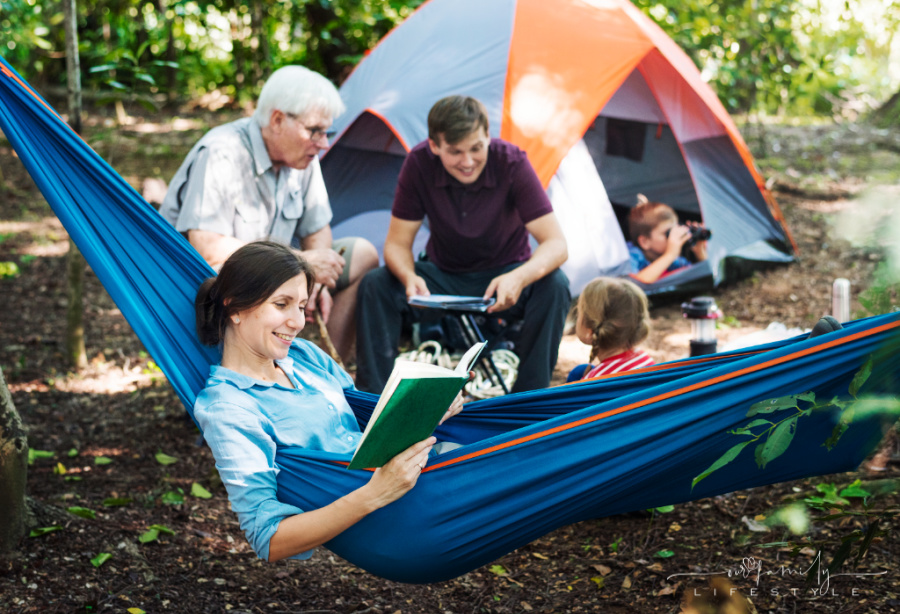 family camping in the forest with mom in hammock and grandpa and dad with kids