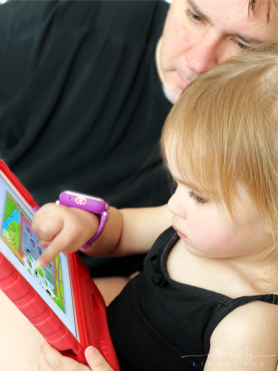 toddler playing ABCmouse games on iPad with grandfather