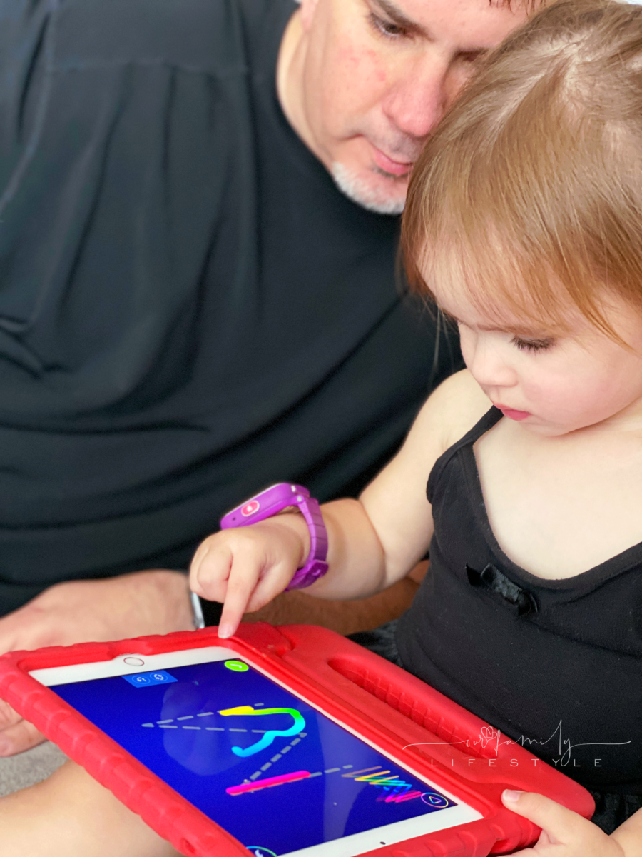 toddler tracing letters on ABCmouse on iPad with grandpa