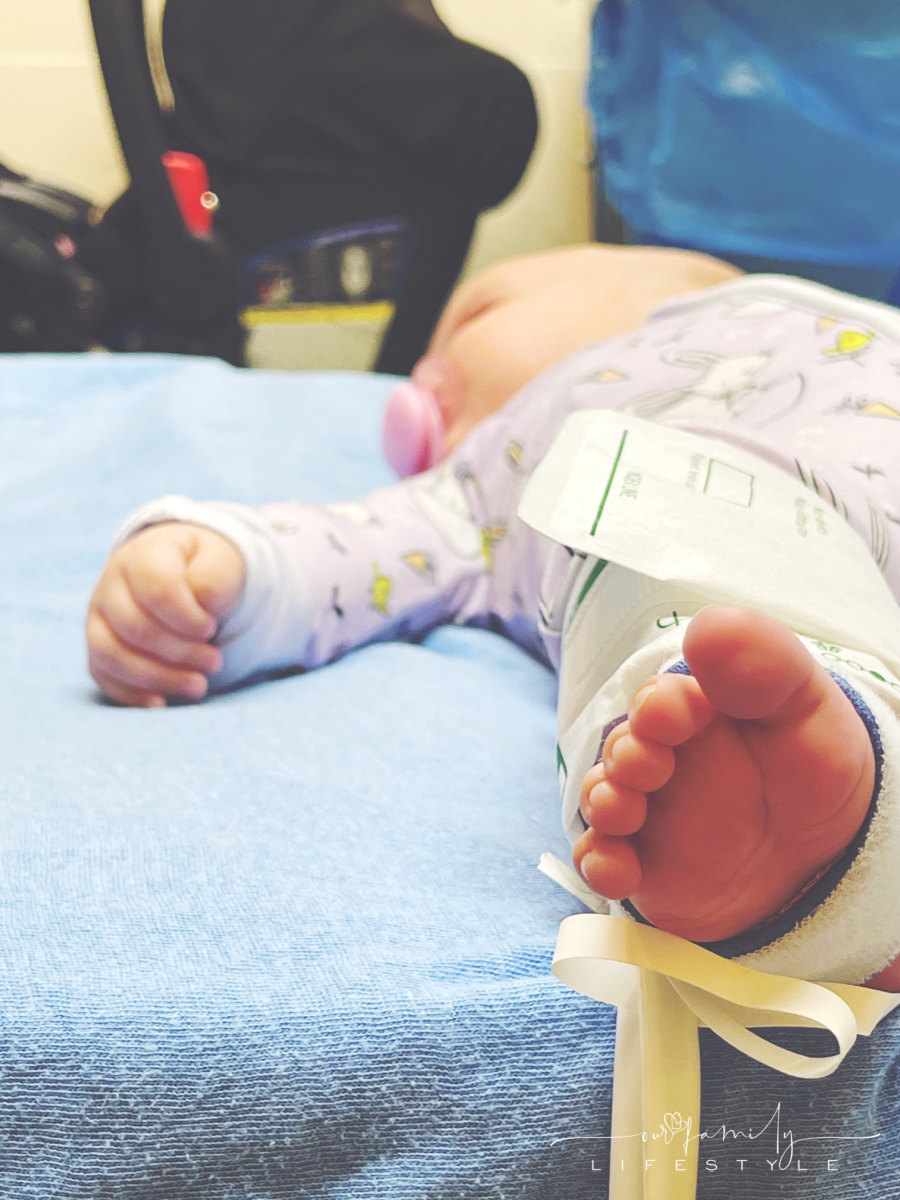 baby laying in hospital bed with blood pressure cough on foot