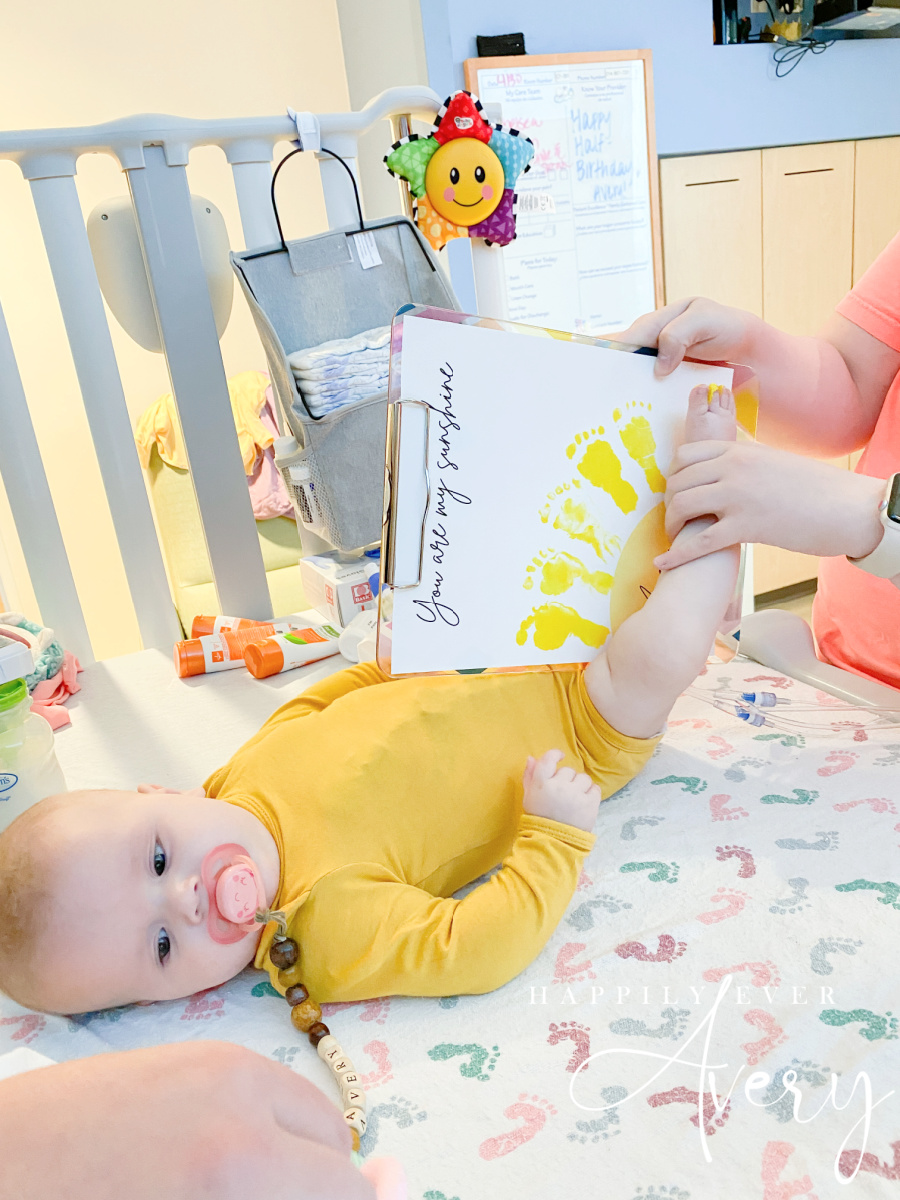 infant in yellow bodysuit doing footprint with paint in hospital