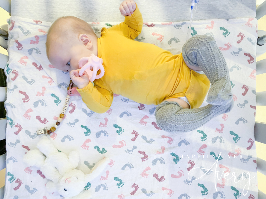 infant in yellow sleeper with teether laying in hospital crib