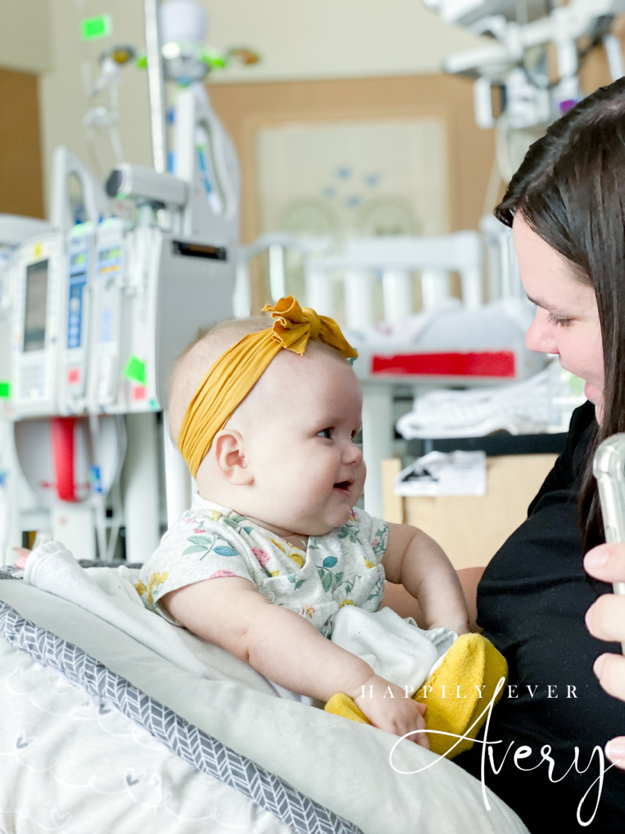infant with yellow bow on her head laughing at mom in hospital room