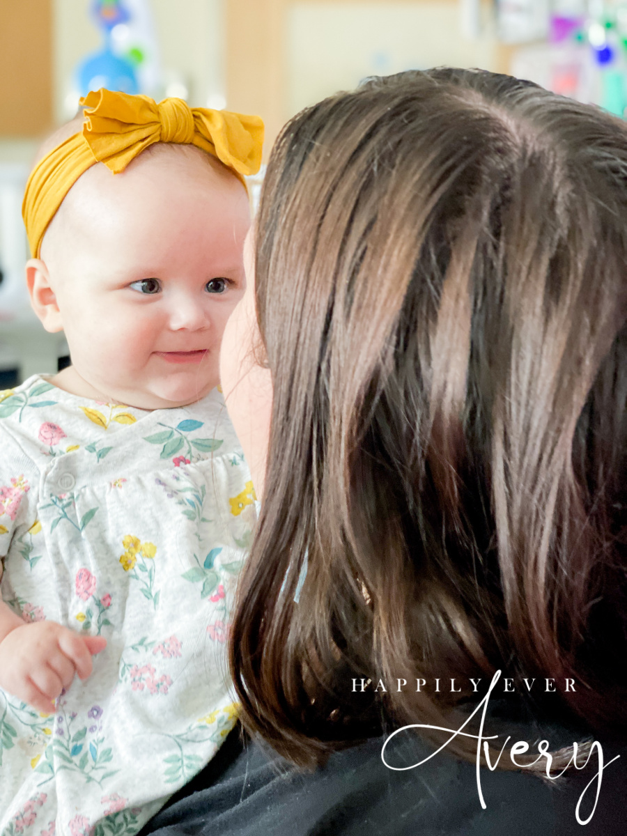 infant with yellow bow smiling at her mother