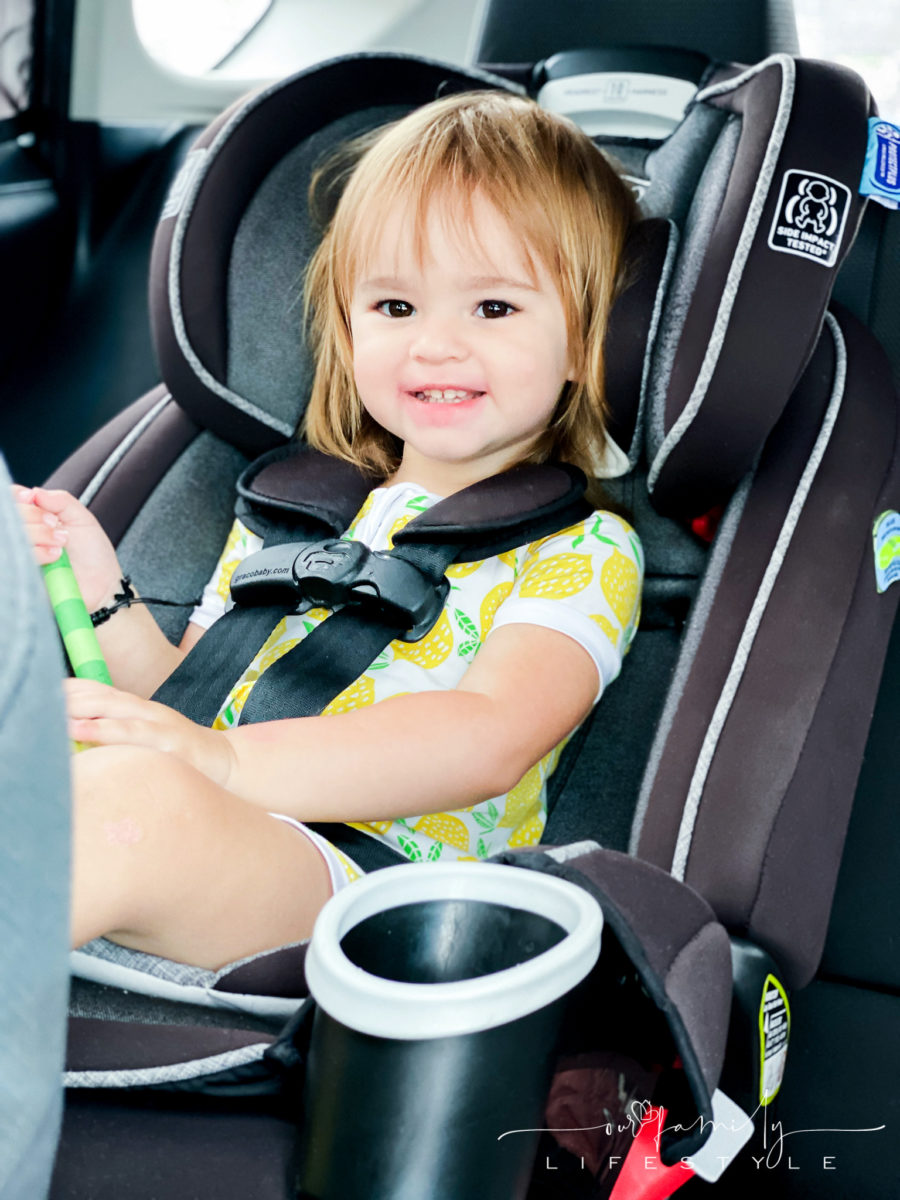 toddler in car seat smiling while holding a large green crayon