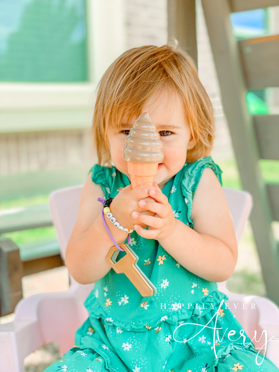 toddler in green dress with bees and flowers on it holding a plastic ice cream cone