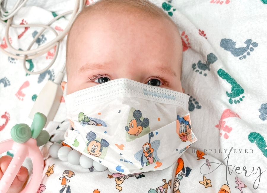 infant with face mask in hospital bed with a toy