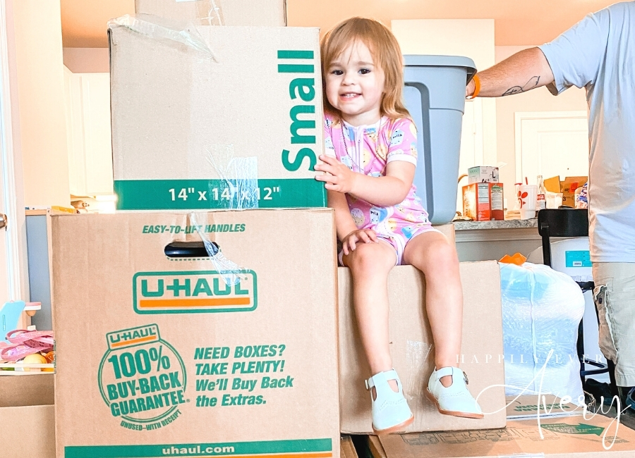 toddler sitting on a stack of moving boxes