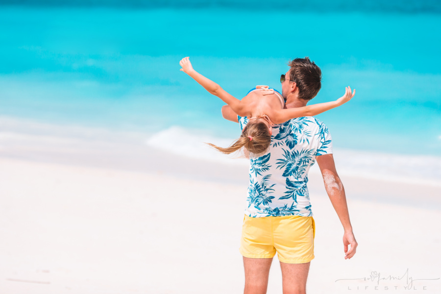 Happy father and his adorable little daughter at white sandy beach having fun