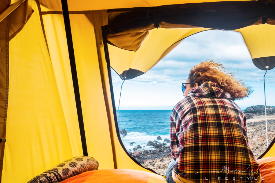 view-of-woman-sitting-outside-tent-on-rocky-beach