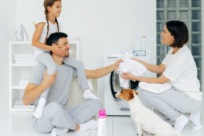 family of mom dad daughter in laundry room with dog