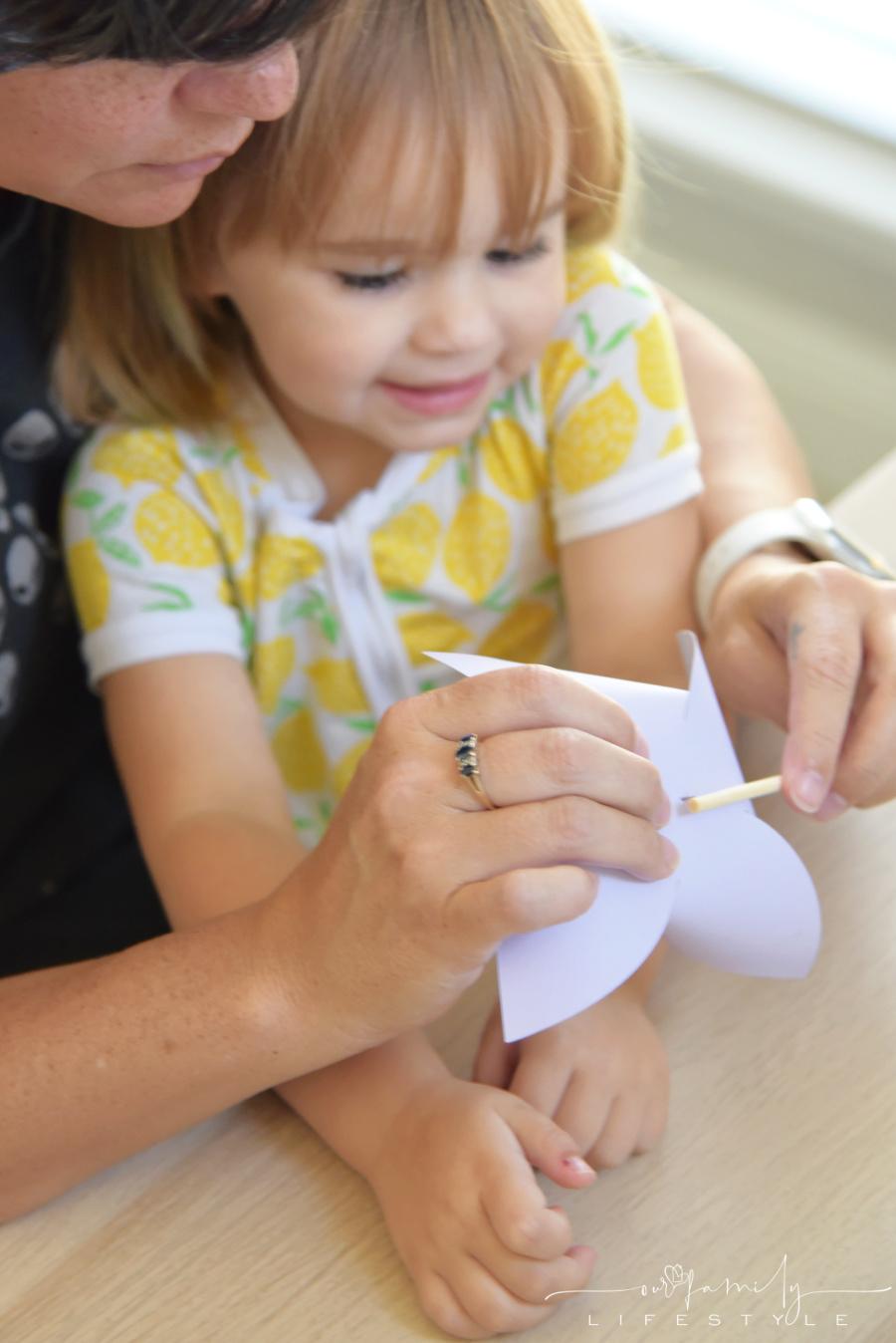 grandma and toddler making paper pinwheels with thumbtack