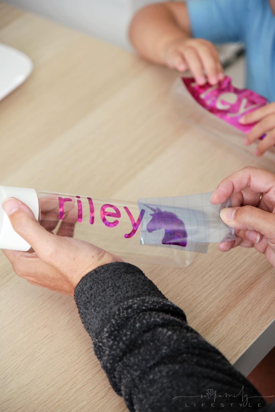 peeling Cricut transfer paper to reveal permanent vinyl on bottle