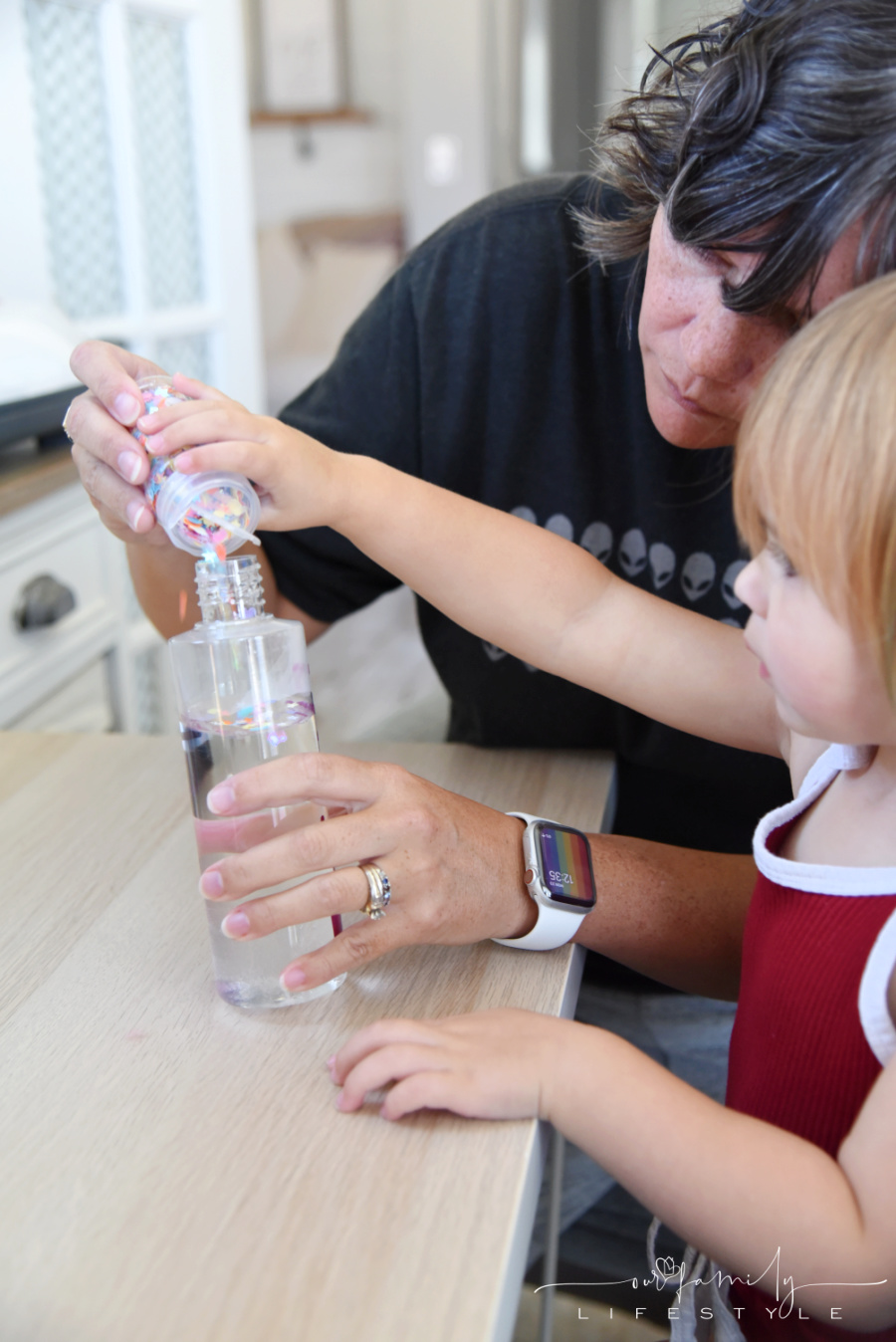 toddler helping pour unicorn glitter into plastic calming bottle