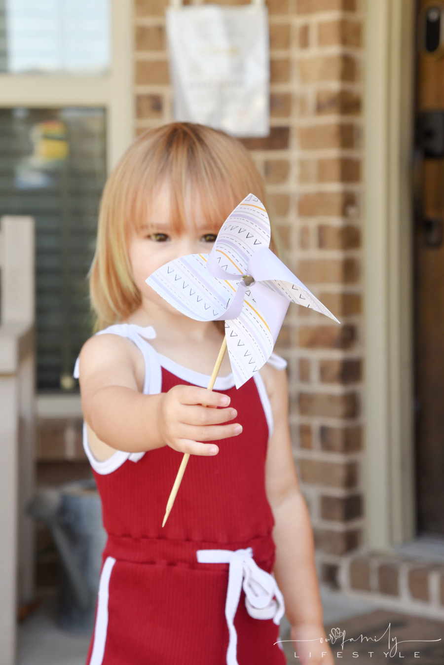 toddler holding DIY pinwheel