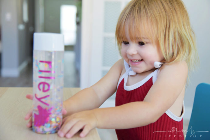 toddler playing with personalized calm down jar