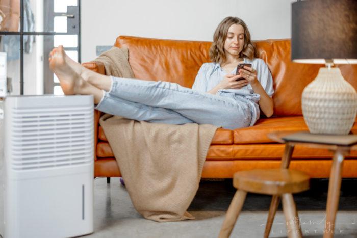woman-sitting-near-air-purifier-monitoring-air-quality-phone