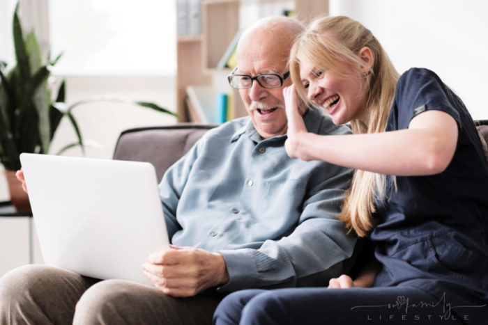 happy-old-man-in-home-caregiver-having-video-call-laptop