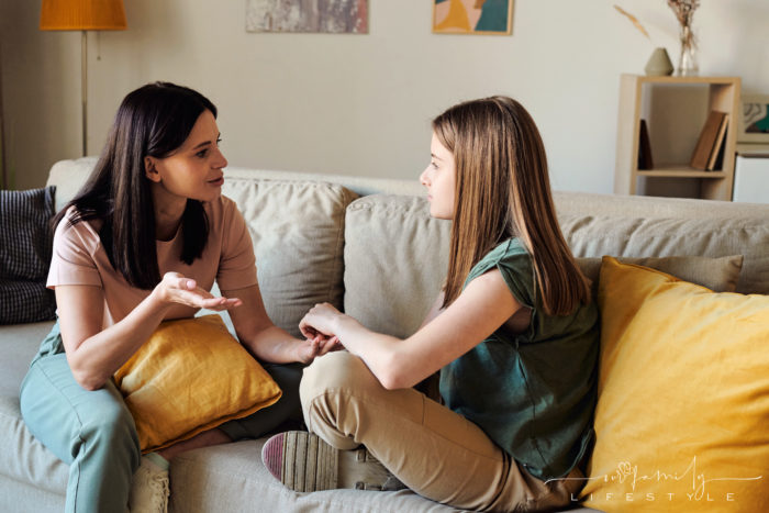 mom-holding-yellow-pillow-discussing-periods-with-daughter-while-both-sitting-couch