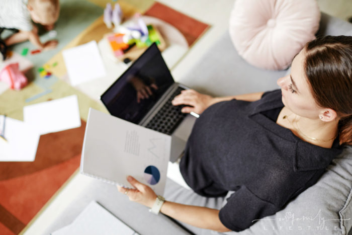 pregnant-mother-looking-over-family-budget-at-home