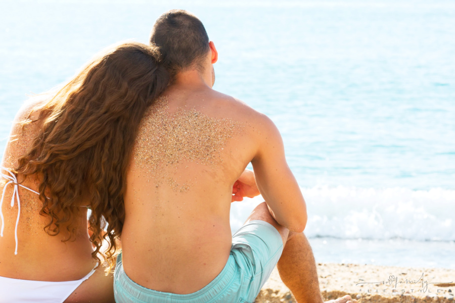 couple sitting on beach watching waves